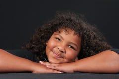 Glückliches Mädchen aufgeworfen auf gekreuzten Händen Stockfoto