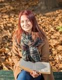 Glückliches Mädchen, das auf Bank im Park sitzt Stockfotografie