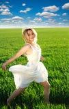 Glückliches Mädchen, das auf dem grünen blühenden Feld unter blauen Himmel läuft Lizenzfreies Stockfoto