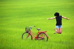 Glückliches Mädchen, das auf dem grünen Gebiet springt Lizenzfreie Stockfotografie