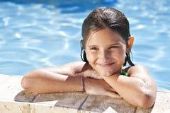 Glückliches Mädchen, das auf dem Rand eines Swimmingpools sich lehnt Stockfoto