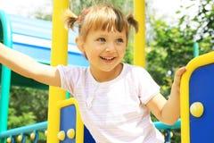 Glückliches Mädchen, das auf dem Spielplatz spielt Lizenzfreies Stockfoto