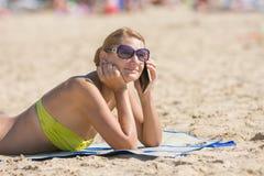Glückliches Mädchen, das auf dem Strand ein Sonnenbad nimmt und am Telefon spricht Stockfotos