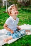 Glückliches Mädchen, das auf der Tablette spielt Mädchen, das eine Tablette verwendet Stockfoto
