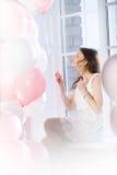 Glückliches Mädchen, das auf einem Fensterbrett mit Ballonen sitzt Stockfotos