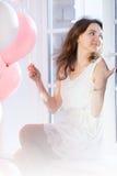 Glückliches Mädchen, das auf einem Fensterbrett sitzt Stockbilder