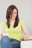 Glückliches Mädchen, das auf einem Sofa unter Verwendung eines Tabletten-PC sitzt und eine Schale hält Stockfotos
