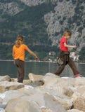 Glückliches Mädchen, das auf Felsen nahe Meer spielt Stockfoto