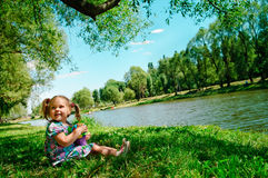 Glückliches Mädchen, das auf Flussquerneigung sitzt Stockbild