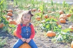 Glückliches Mädchen, das auf Kürbis am Bauernhoffeldflecken sitzt Stockfoto
