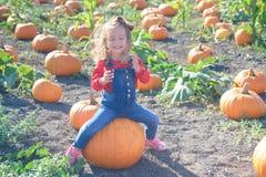 Glückliches Mädchen, das auf Kürbis am Bauernhoffeldflecken sitzt Lizenzfreie Stockbilder