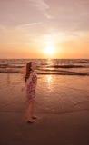 Glückliches Mädchen, das auf schönem Strand bei Sonnenuntergang sich entspannt Stockbild