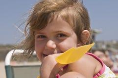 Glückliches Mädchen, das auf Strand spielt Stockfoto