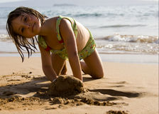 Glückliches Mädchen, das auf Strand spielt Stockbild