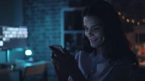 Glückliches Mädchen, das aufpassenden Inhalt des Smartphone auf Schirm im dunklen Büro nachts verwendet stock video footage