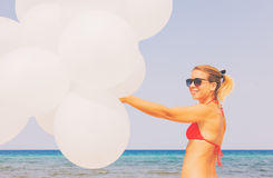 Glückliches Mädchen, das Bündel weiße Luftballone hält Lizenzfreies Stockbild