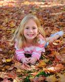 Glückliches Mädchen, das in Blätter legt Lizenzfreie Stockfotos
