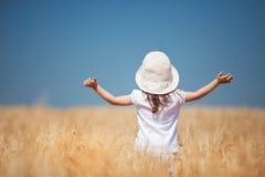 Glückliches Mädchen, das in den goldenen Weizen, das Leben genießend geht lizenzfreies stockbild