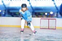 Glückliches Mädchen, das den Kobold während des Hockeyspiels führt stockfoto