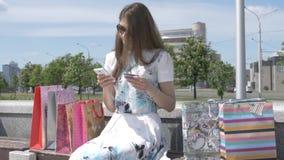 Glückliches Mädchen, das ein intelligentes Telefon in der Straße sitzt auf einer Bank verwendet stock video