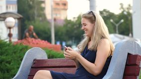 Glückliches Mädchen, das ein intelligentes Telefon in einem Stadtpark sitzt auf einer Bank verwendet stock footage