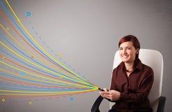 Glückliches Mädchen, das ein Telefon mit bunten abstrakten Zeilen anhält Stockfoto