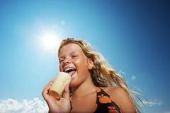 Glückliches Mädchen, das Eiscreme isst Stockfotos
