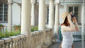 Glückliches Mädchen, das Foto mit Retro- Kamera auf Stadtstraße macht stock footage