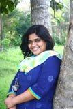 Glückliches Mädchen, das fröhliches Lächeln in der Natur Backgroud gibt Stockfotos