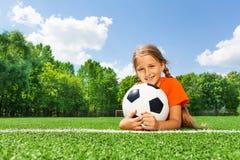 Glückliches Mädchen, das Fußball mit beiden Armen hält Lizenzfreie Stockbilder
