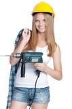 Glückliches Mädchen, das gelben harten Hut mit Bohrgerät trägt lizenzfreie stockbilder