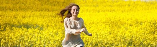 Glückliches Mädchen, das in gelbes Blumenfeld läuft Stockbild