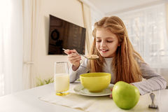 Glückliches Mädchen, das Getreide in der Küche isst Lizenzfreie Stockbilder