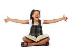 Glückliches Mädchen, das hinter altem Buch lächelt Lizenzfreie Stockfotos