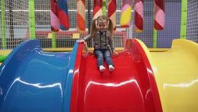Glückliches Mädchen, das hinunter Dia auf Spielplatz in der Mitte der Kinder umzieht stock video footage