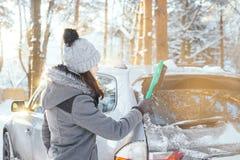 Glückliches Mädchen, das ihr Auto des Schnees im Winter säubert stockbild