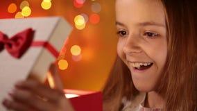 Glückliches Mädchen, das ihr Weihnachtsgeschenk öffnet stock footage