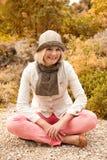Glückliches Mädchen, das im Herbstpark sitzt Lizenzfreies Stockbild