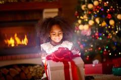 Glückliches Mädchen, das im offenen magischen Weihnachtsgeschenk schaut Lizenzfreies Stockfoto
