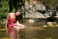 Glückliches Mädchen, das im Wasser mit rotem Kleid sitzt Stockfoto