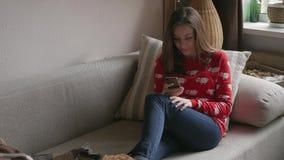 Glückliches Mädchen, das Inhalt auf Linie in einem intelligenten Telefon strömend zu Hause sitzt auf einem Sofa im Winter aufpass stock video