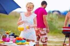 Glückliches Mädchen, das Lebensmittel auf Picknicktisch zubereitet Stockbild