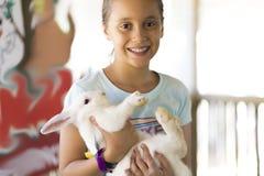 Glückliches Mädchen, das mit Kaninchen spielt Stockbilder