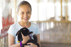 Glückliches Mädchen, das mit Kaninchen spielt Stockfotografie