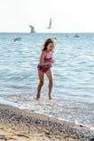 Glückliches Mädchen, das mit Möven auf dem Strand läuft Stockbilder
