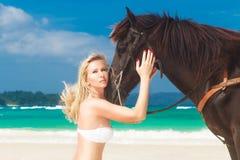 Glückliches Mädchen, das mit Pferd auf einem tropischen Strand geht Lizenzfreie Stockbilder