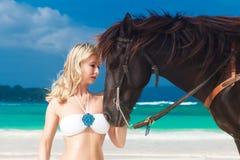 Glückliches Mädchen, das mit Pferd auf einem tropischen Strand geht Stockfotografie