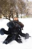 Glückliches Mädchen, das mit Schnee spielt Stockbilder