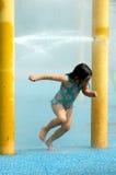 Glückliches Mädchen, das mit Wasser spielt stockfoto