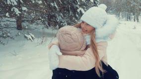 Glückliches Mädchen, das in Mutterumarmungen im schneebedeckten Wald während Winterwegzeitlupe läuft stock video footage